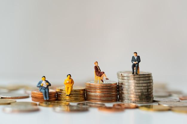 Miniaturowi ludzie, biznesowy drużynowy obsiadanie na stertowych monetach używać jako biznesowa praca zespołowa i pieniężny pojęcie Premium Zdjęcia