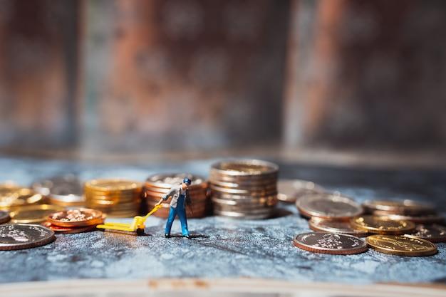 Miniaturowi Ludzie, Mężczyzna Ciągnący Stos Monet Premium Zdjęcia