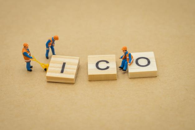 Miniaturowi ludzie naprawa robotnika budowlanego za pomocą drewnianego słowa ico (początkowa oferta monet) Premium Zdjęcia