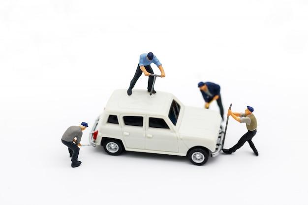 Miniaturowi Ludzie: Pracownicy Naprawiający Samochód. Serwis Samochodowy, Naprawa, Koncepcja Konserwacji. Premium Zdjęcia