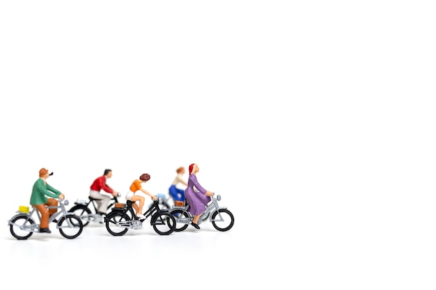 Miniaturowi ludzie: przyjaciel grupy przejażdżki bicykl odizolowywa na białym tle Premium Zdjęcia