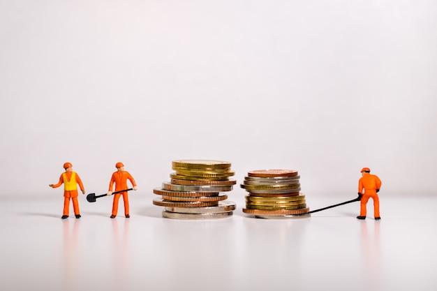 Miniaturowi ludzie, technik pracuje na stosie monet Premium Zdjęcia