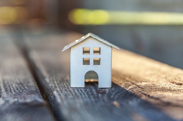 Miniaturowy biel zabawki modela dom w drewnianym tle. eco village, streszczenie tło środowiska Premium Zdjęcia