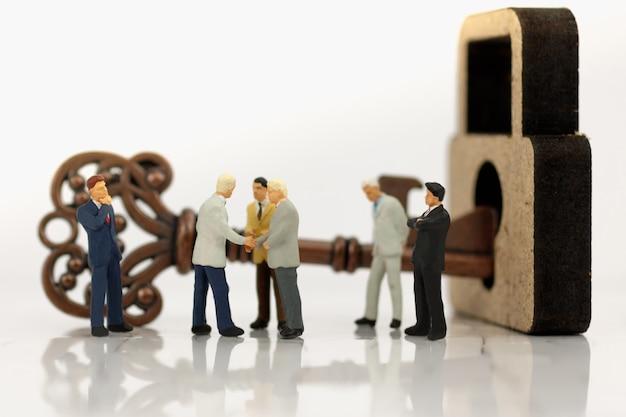 Miniaturowy biznesmen uścisk dłoni z odblokować klucze. Premium Zdjęcia