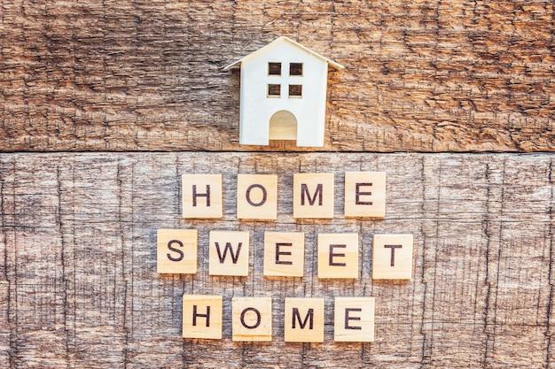 Miniaturowy Domek Zabawkowy Z Napisem Home Sweet Home Słowem Na Drewnianym Stole Premium Zdjęcia