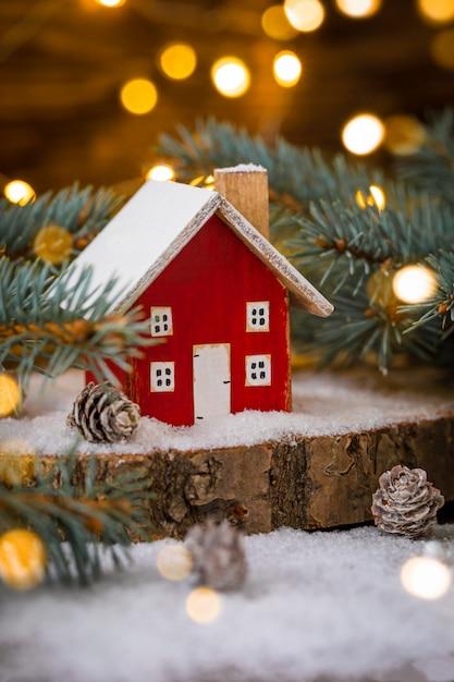 Miniaturowy drewniany dom na śniegu nad niewyraźną świąteczną dekoracją Premium Zdjęcia