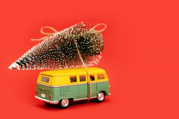 Miniaturowy hipisa samochód z jedlinowym drzewem na czerwonym tle Premium Zdjęcia