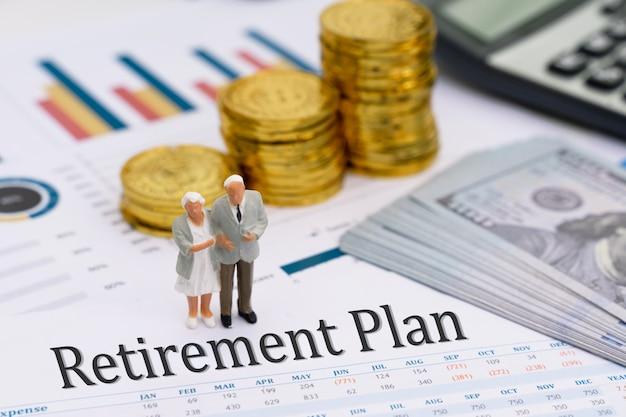 Miniaturowy model starszej pary stojącej na raporcie planu emerytalnego Premium Zdjęcia