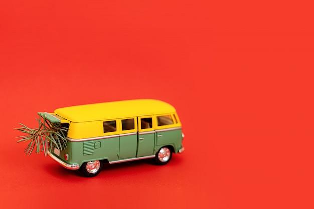 Miniaturowy samochód hipisowski 2019 z jodły na czerwonym tle Premium Zdjęcia