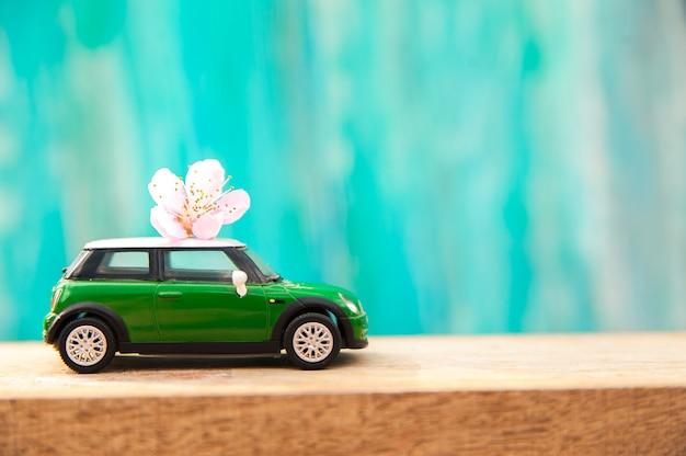 Miniaturowy Samochód Na Tle Kwitnie Drzewo W Wiośnie. Premium Zdjęcia