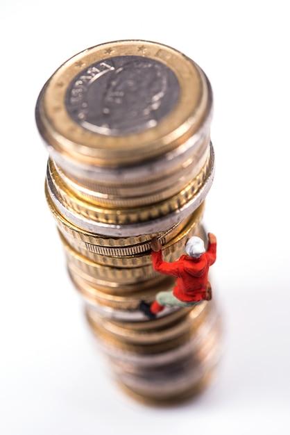 Miniaturowy wspinacz wspinaczka na stos monet Premium Zdjęcia