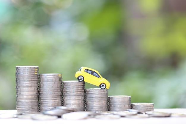 Miniaturowy żółty model samochodu na uprawy stos monet pieniędzy na tle przyrody zielone Premium Zdjęcia