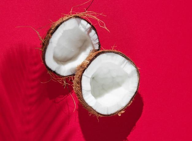 Minimalistyczna Tropikalna Martwa Natura. Dwie Połówki Posiekanego Kokosa Z Cieniami Z Liści Palmowych Na Czerwonym Tle. Kreatywna Koncepcja Mody. Premium Zdjęcia