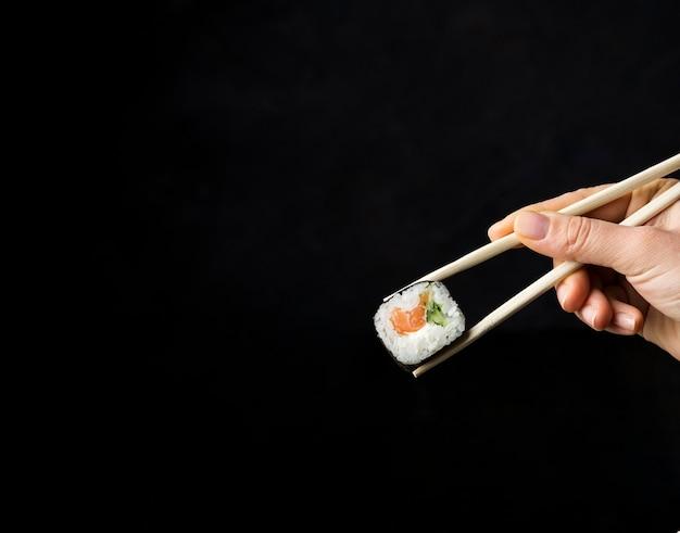 Minimalistyczne Sushi Roll Z Warzywami I Ryżem Na Czarnym Tle Premium Zdjęcia