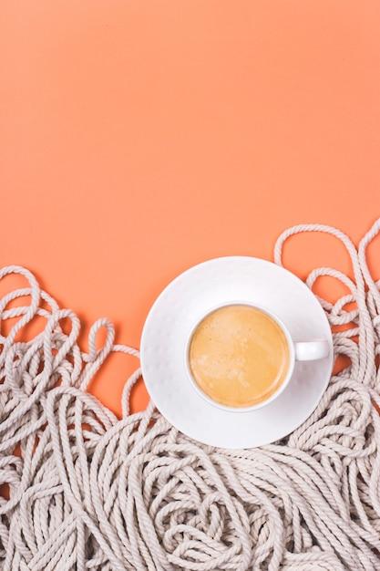 Minimalistyczny Bawełniany Biały Linowy Tło Z Filiżanką Cappuccino Na Koralowym Kolorowym Tle. Premium Zdjęcia