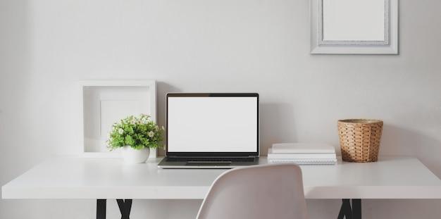 Minimalna Przestrzeń Robocza Z Otwartym Laptopem Z Pustym Ekranem I Makietą Premium Zdjęcia