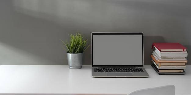 Minimalne Biuro Domowe Z Otwartym Laptopem Z Pustym Ekranem, Stosem Książek I Donicą Premium Zdjęcia