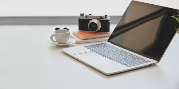 Minimalne miejsce pracy fotografa z otwartym laptopem, zabytkowym aparatem i filiżanką kawy Premium Zdjęcia