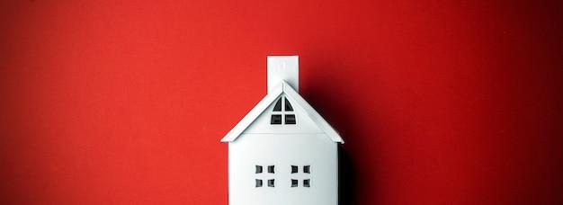 Minimalne Tło Boże Narodzenie Z Białym Dekoracyjnym Domem Na Czerwonym Tle. Minimalna Koncepcja. Premium Zdjęcia