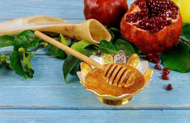 Miód W Misce Z Patyczkiem I Granatami Premium Zdjęcia
