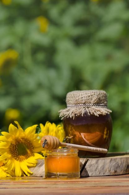 Miód W Szklanych Słoikach I Zachodnia Pszczoła Miodna. Pszczoła Miodna. Pszczoła Siedzi Na Szklance Miodu. Chochla I Miód W Słoiku Premium Zdjęcia