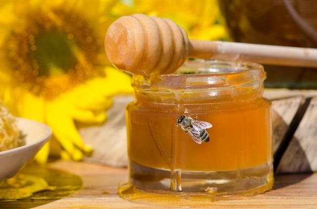 Miód W Szklanych Słoikach I Zachodnia Pszczoła Miodna. Pszczoła Miodna. Pszczoła Siedzi Na Szklance Miodu. Miód W Szklanym Słoju Z Latającą Pszczołą Miodną Premium Zdjęcia