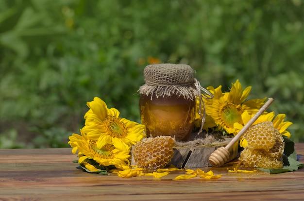 Miód Z Miodową Chochlą Na Drewnianym Stole. Organiczny Kwiatowy Miód Przeciwko Niewyraźnej Naturze Z Kwiatami. Skopiuj Miejsce Na Tekst Premium Zdjęcia