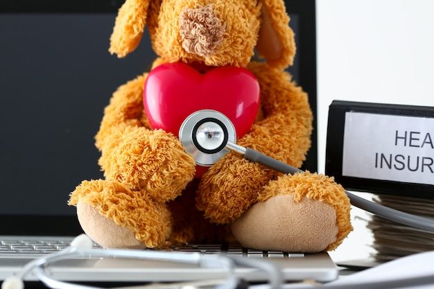 Miś trzyma zabawkowe czerwone serce słuchania z głową fonendoskopu Premium Zdjęcia