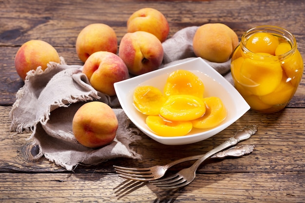 Miska Brzoskwiń W Puszkach Ze świeżymi Owocami Na Drewnianym Stole Premium Zdjęcia