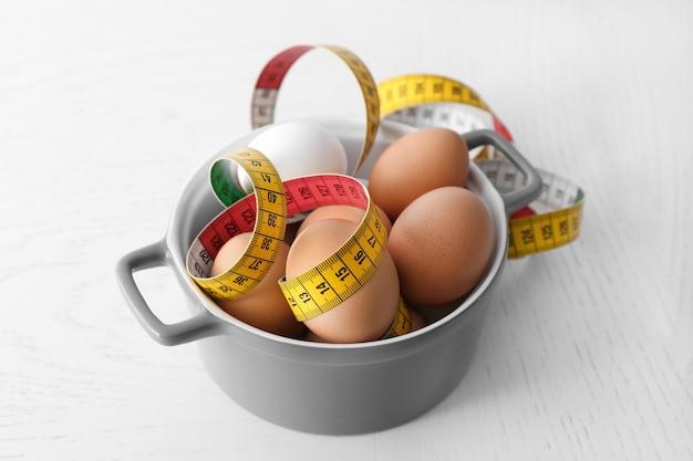 Miska Z Jajkami I Miarką Na Stole. Pojęcie Odżywiania Premium Zdjęcia