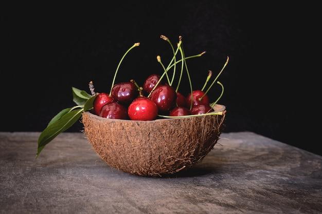 Miska Z łupin Orzecha Kokosowego Pełna świeżych Wiśni W łupinach Na Drewnianym Stole Na Czarno Premium Zdjęcia