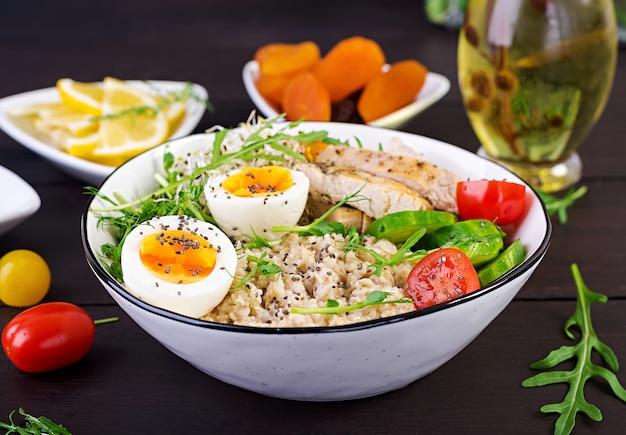 Miska Z Płatkami Owsianymi, Filetem Z Kurczaka, Pomidorem, Sałatą, Mikrogreenami I Gotowanym Jajkiem Premium Zdjęcia