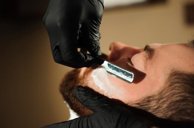 Mistrz ścina włosy i brodę mężczyzn w zakładzie fryzjerskim Premium Zdjęcia