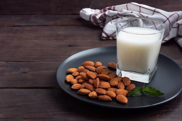 Mleko Migdałowe W Szklanych Szklankach Na Ciemnym Drewnianym Stole. Premium Zdjęcia