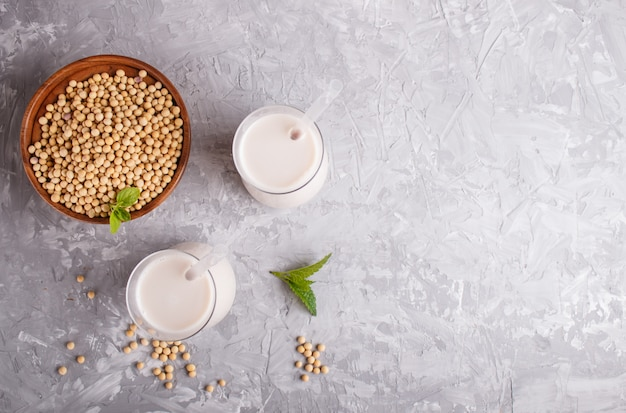 Mleko sojowe ekologiczne bez mleka w szklanej i drewnianej płytce z soją na szarym betonie. Premium Zdjęcia