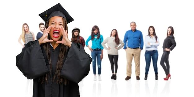 Młoda Absolwentka Czarnej Kobiety W Warkoczach Krzyczała Wściekła, Wyrażała Szaleństwo I Niestabilność Umysłową, Otwierała Usta I Na Wpół Otwarte Oczy, Koncepcja Szaleństwa Premium Zdjęcia