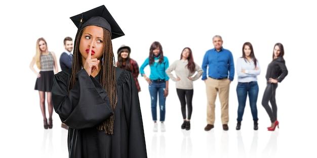 Młoda Absolwentka Czarnoskórej Kobiety Warkoczach Utrzymywała Tajemnicę Lub Prosiła O Ciszę, Poważną Twarz, Posłuszeństwo Premium Zdjęcia