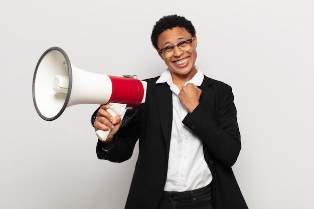 Młoda Afro Kobieta Czuje Się Szczęśliwa, Pozytywna I Odnosząca Sukcesy, Zmotywowana, Gdy Staje Przed Wyzwaniem Lub świętuje Dobre Wyniki Premium Zdjęcia