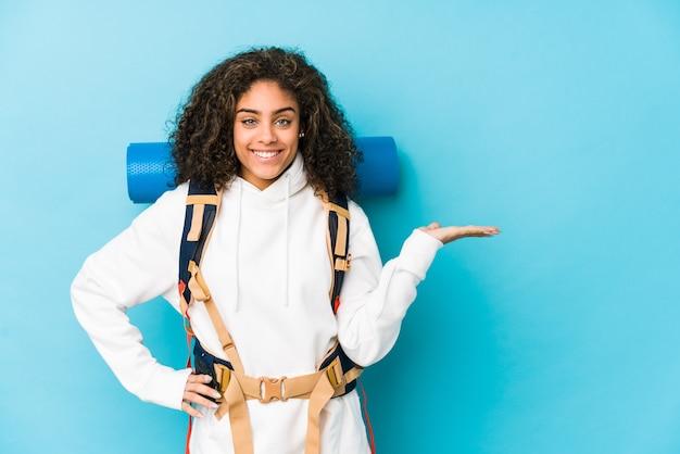 Młoda Afroamerykanin Kobieta Z Plecakiem, Pokazując Miejsce Na Kopię Na Dłoni I Trzymając Drugą Rękę Na Talii. Premium Zdjęcia