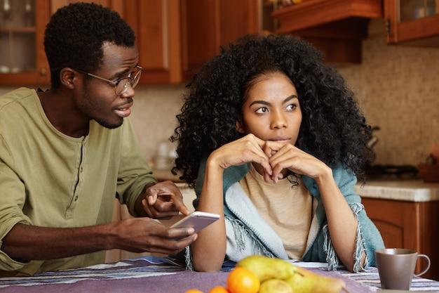 Młoda Afroamerykańska Rodzina Walczy W Kuchni Z Powodu Romansu. Mężczyzna W Okularach Trzymający Telefon Komórkowy, Wskazujący Palcem Na Ekran, Próbujący Wyjaśnić Sobie Miłosne Wiadomości Od Nieznanej Kobiety Darmowe Zdjęcia