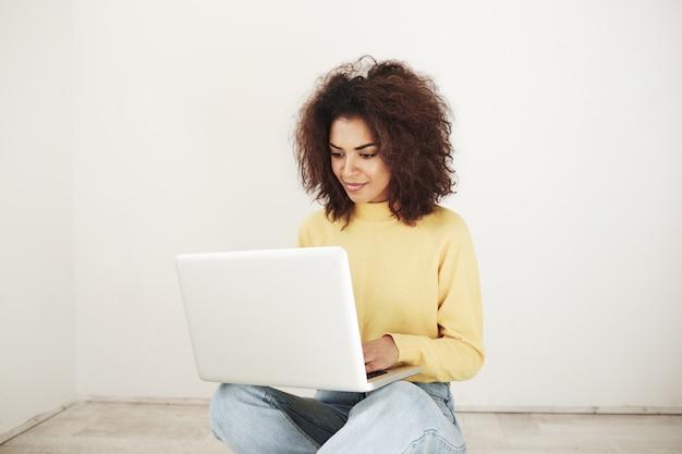 Młoda Afrykańska Kobieta Ono Uśmiecha Się Patrzejący Laptopu Obsiadanie Na Podłoga Darmowe Zdjęcia
