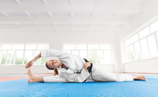 Młoda aktywna dziewczyna robi ćwiczeniu na elastyczności w lekkim gym. Premium Zdjęcia