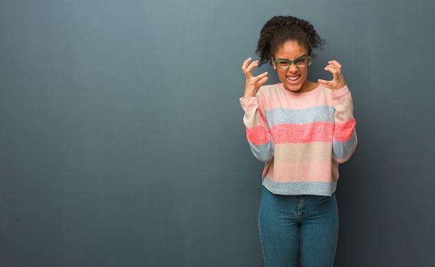 Młoda amerykanin afrykańskiego pochodzenia dziewczyna z niebieskimi oczami gniewnymi i zdenerwowanymi Premium Zdjęcia