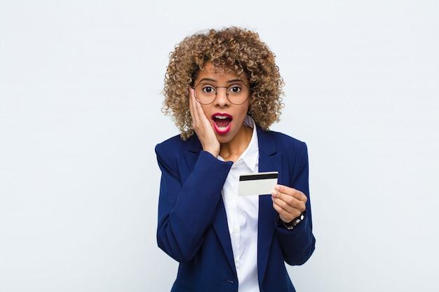 Młoda Amerykanin Afrykańskiego Pochodzenia Kobieta Czuje Się Szczęśliwa, Podekscytowana I Zaskoczona, Patrząc Z Boku Obiema Rękami Na Twarzy Za Pomocą Karty Kredytowej Premium Zdjęcia