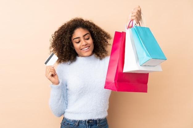 Młoda Amerykanin Afrykańskiego Pochodzenia Kobieta Na Beżowej ściany Mienia Torba Na Zakupy I Karcie Kredytowej Premium Zdjęcia