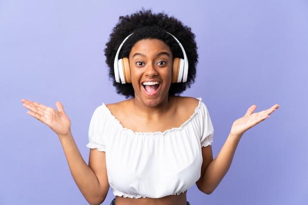 Młoda Amerykanin Afrykańskiego Pochodzenia Kobieta Odizolowywająca Na Purpurowym Tle Zaskakująca I Słuchająca Muzyka Premium Zdjęcia