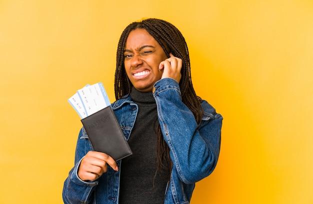Młoda Amerykanin Afrykańskiego Pochodzenia Kobieta Trzyma Paszport Odizolowywał Nakrywkowych Ucho Z Rękami. Premium Zdjęcia