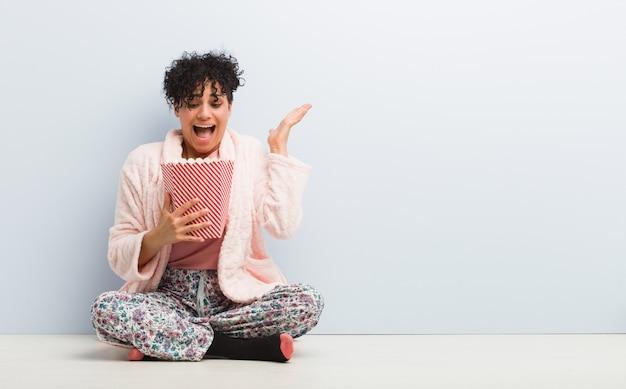 Młoda Amerykanin Afrykańskiego Pochodzenia Kobieta Trzyma Popkorn Wiadro świętuje Zwycięstwo Premium Zdjęcia