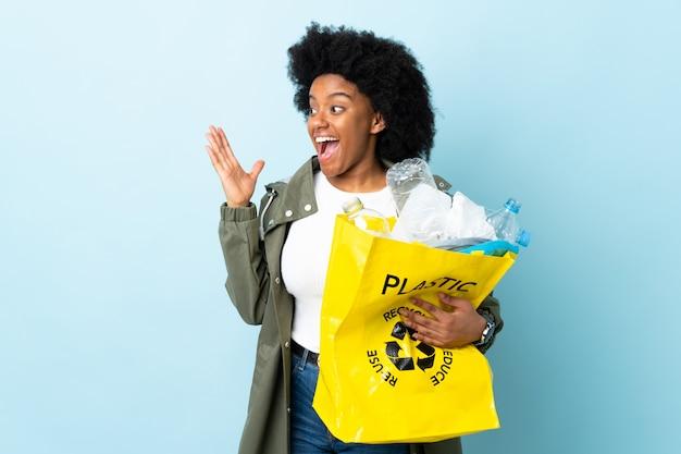 Młoda Amerykanin Afrykańskiego Pochodzenia Kobieta Trzyma Przetwarzającą Torbę Odizolowywająca Na Kolorowym Tle Z Niespodzianka Wyrazem Twarzy Premium Zdjęcia
