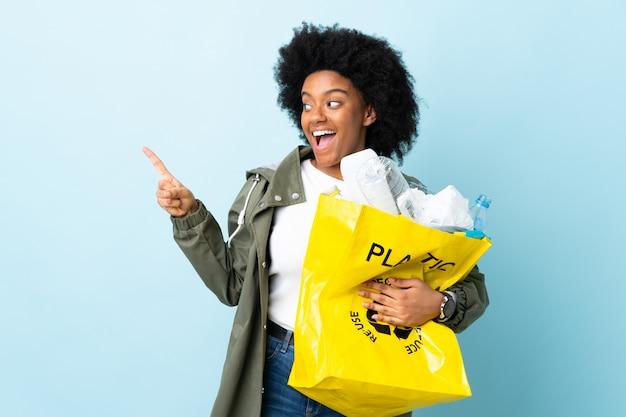 Młoda Amerykanin Afrykańskiego Pochodzenia Kobieta Trzyma Przetwarzającą Torbę Odizolowywająca Na Kolorowym Tle Zaskakującym I Wskazuje Stronę Premium Zdjęcia
